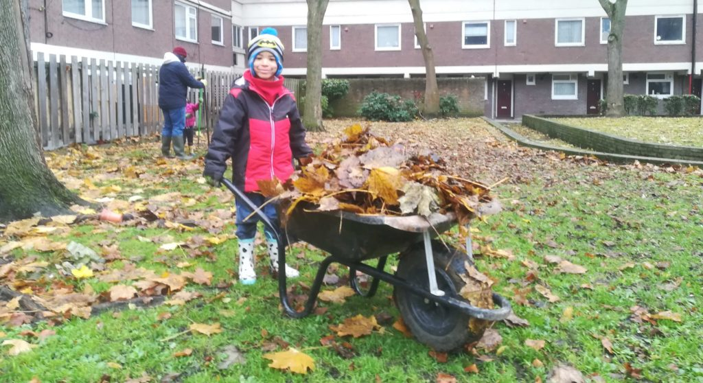 child with wheelbarrow gardening on Lambeth council estates